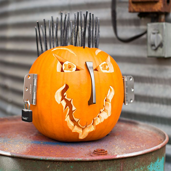 A pumpkin with electrical wire hair, a drawer pull nose, door hinge ears and a padlock earring.