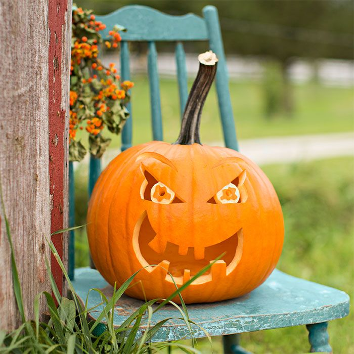 A pumpkin carved with glaring eyes and a wide open, toothy mouth set on a turquoise chair.