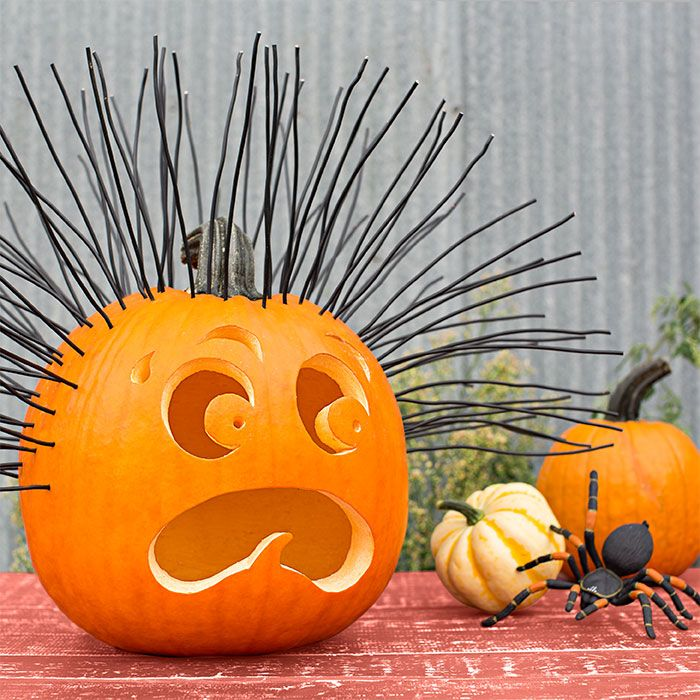 A pumpkin with a scared face and black wire hair looking at a toy spider.