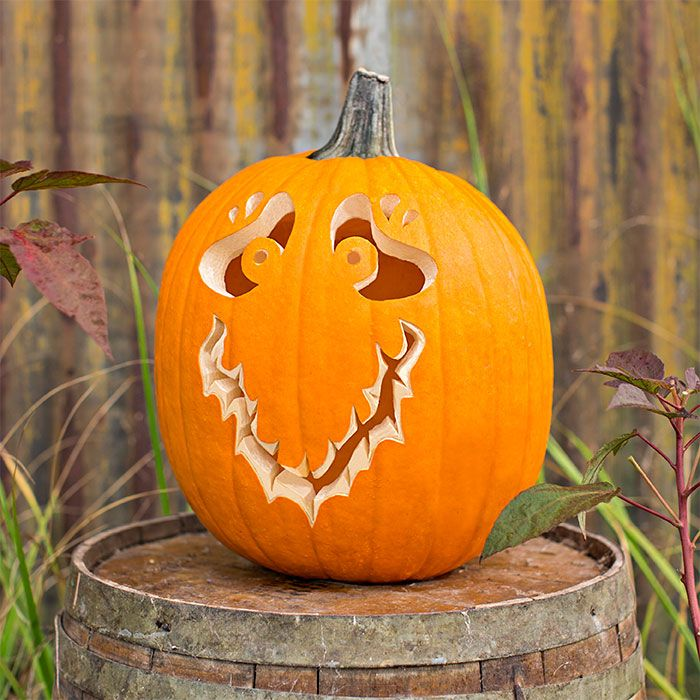 A pumpkin carved with wide eyes and a large v-shaped smile resting on a wooden barrel.