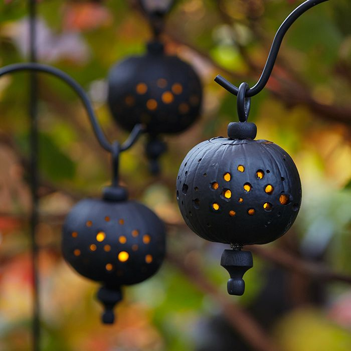 Three black pumpkins acting as lanterns, with holes drilled to show the glow of L E D lights.