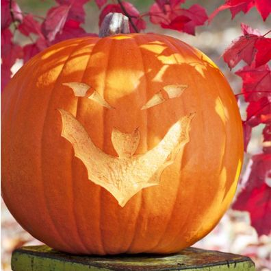 A pumpkin with etched eyes and a grinning mouth etched in the shape of a bat with raised wings.